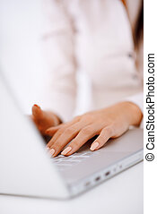 Business woman typing on laptop keyboard - Close up of...