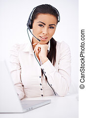 Business woman with headset sitting in front of laptop -...