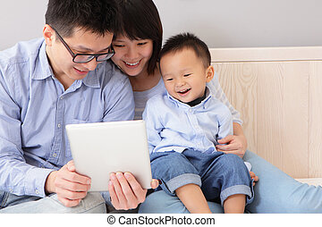 happy family using tablet pc - closeup of a happy, family of...