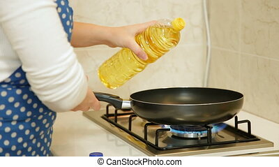 Pouring Oil Into Frying Pan - A woman preparing food at...