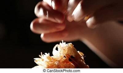 Women's hands are cleaning shrimp. Macro shot backlit.