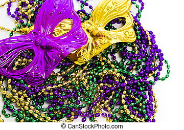 Mardi Gras beads and colorful mask on white backgound.