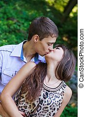 In love couple kiss in a summer green park