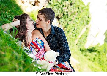 Cheerful happy couple flirt in a sunny summer park