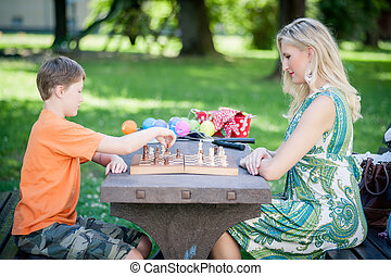 Woman playing Chess with her Son