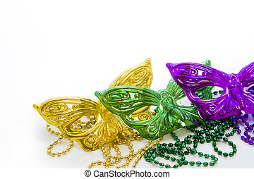 Mardi Gras beads and colorful masks on white backgound