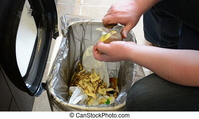 man hands peel potatoes. paring fall into waste bin.
