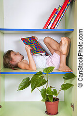 child reading a book in a bookcase - child reading a book...