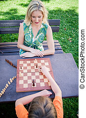 Mother and Son playing Chess in a Park