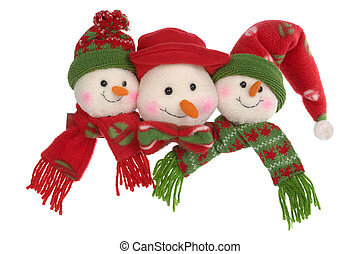 snowman - Three toy snowballs in caps and scarfs on a white...