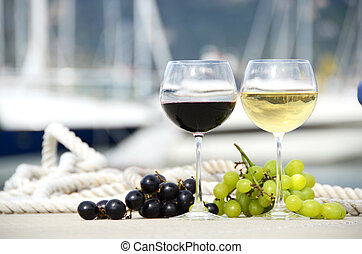 Pair of wineglasses and grapes against the yacht pier of La...