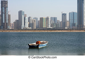 Sharjah cityscape - The boat and modern buildings at Sharjah
