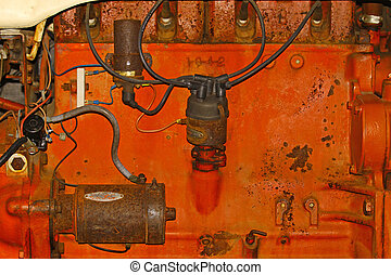 An old orange farm tractor engine block and components