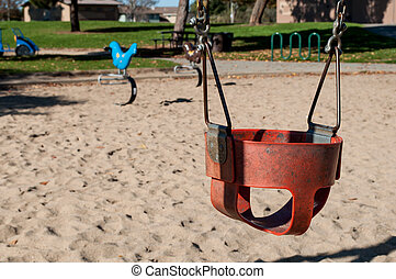 empty swing in outside playground - isolated empty infant...