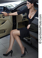 Elegant woman with long legs in car - Sexy woman in luxury...