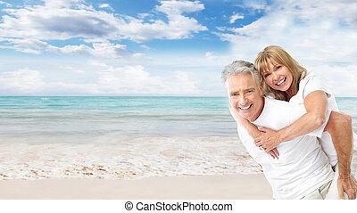 Happy senior couple on the beach. Exotic luxury resort.