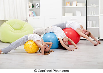 Kids and woman doing stretching exercises - using large...