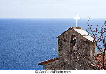A bell tower, the sea and the sky - Church bell tower in...