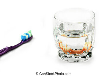 Dental health concept: partial denture inside glass next to...