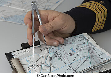 Hand of Captain using a pair of compasses for navigation...