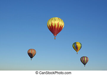 4 hot air balloons floating against a blue sky Albuquerque...