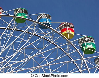 ferris wheel - a colourful fairground wheel against a blue...