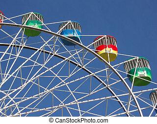 ferris wheel - a colourful fairground wheel against a blue...