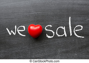 we love sale phrase handwritten on the school blackboard