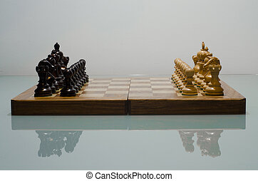chessboard with pieces set up for play shoot on reflective...