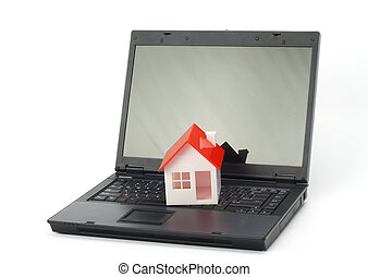 Real property or insurance concept - House model on laptop...