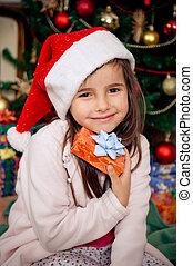 Christmas morning - Cute little girl holding gift box in...