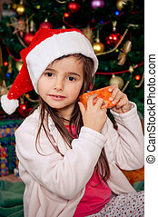 Christmas morning - Cute little girl checking gift box in...