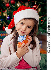 Christmas morning - Cute little girl holding gift box in...