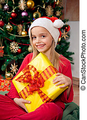 Christmas morning - Cute little girl holding her gift in...