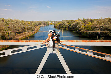 Bride and groom on the bridge over the river