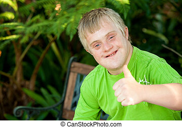 Cute handicapped boy showing thumbs up outdoors. - Close up...