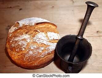 Mortar and bread - Old iron mortar next to newly baked...