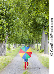 little girl with umbrella in spring alley