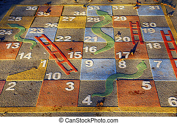 Large outdoor snakes and ladders game in a park