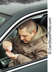 Man sitting in car with drugs in the hands