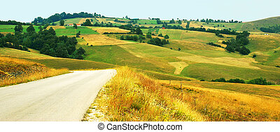 rural landscape - green yellow meadows and fields over hills...