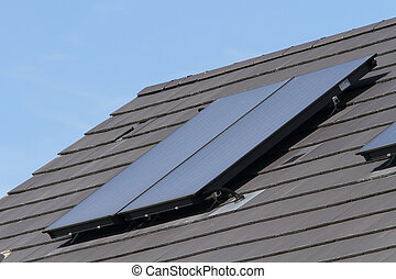 Solar hot water glass panel array on a house roof against a...