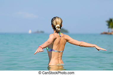 Beautiful young slim girl in the water in the sea, looking...