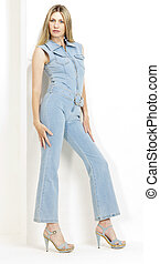 standing woman wearing denim overalls and summer shoes