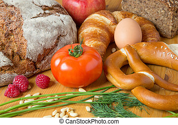 kitchen table with a lot of food like bread and vegetables -...