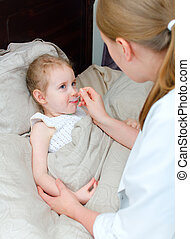 Pediatrician visiting sick child at home and giving medicine