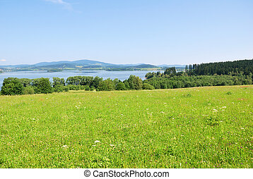Lipno dam reservoir and green hillside country