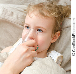 Portrait of little girl lying in bed with inhalator mask on...