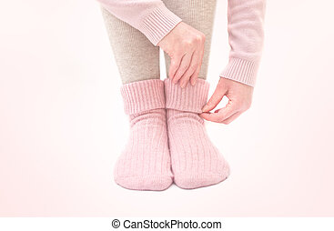 Warm woolen socks - Female legs wearing beautiful warm pink...