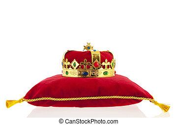 Golden crown on velvet pillow